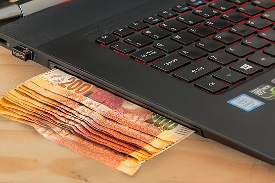 blog niches that make money, image of money under a laptop